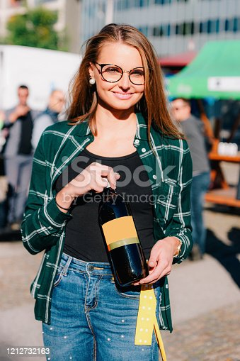 Young smiling girl wearing glasses holds wine bottle. Woman casual style. Female person having fun. Happy holiday celebration. Outdoors lifestyle portrait. Adult beautiful face. Street event