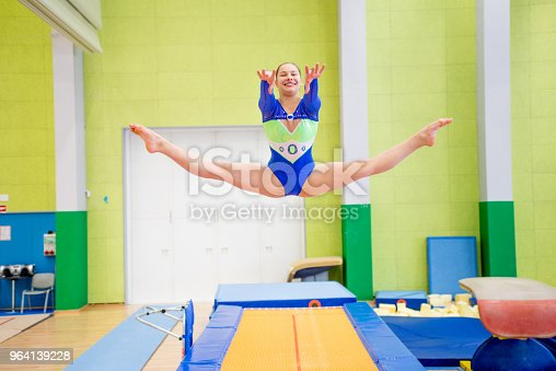 Young Smiling Gymnastics Athlete Doing the Splits in Mid Air.