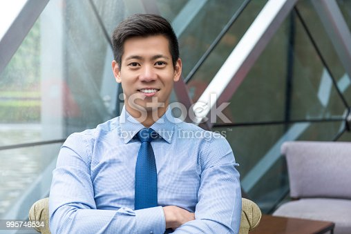 Portrait of young smiling handsome Asian Thai-Chinese businessman sitting with arm crossed in office lounge