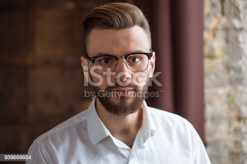 649754038 istock photo Young smiling handsome bearded businessman in a white shirt and glasses stands at the center of the office and looks at the camera. 939669654