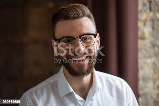 649754038 istock photo Young smiling handsome bearded businessman in a white shirt and glasses stands at the center of the office and looks at the camera. 939669686
