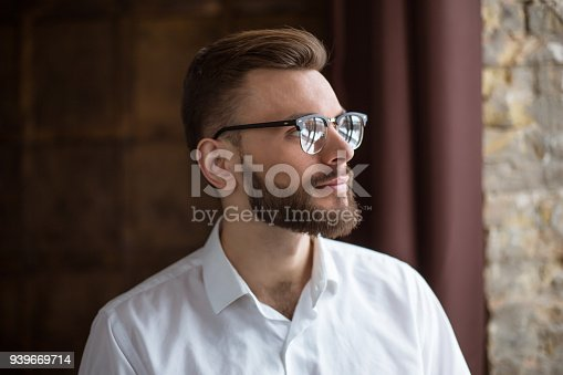 649754038 istock photo Young smiling handsome bearded businessman in a white shirt and glasses stands at the center of the office and looks at the camera. 939669714