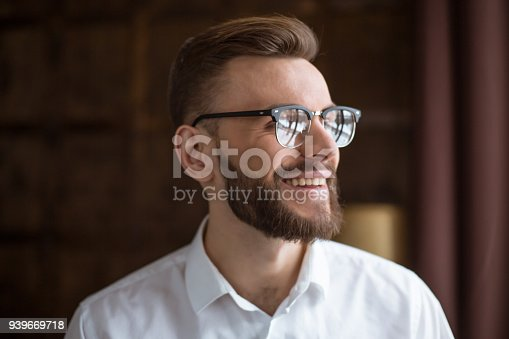 649754038 istock photo Young smiling handsome bearded businessman in a white shirt and glasses stands at the center of the office and looks at the camera. 939669718