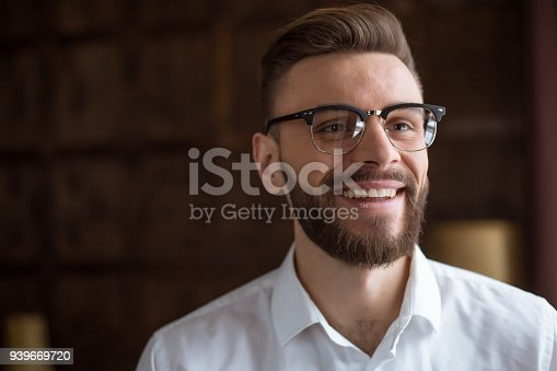 649754038 istock photo Young smiling handsome bearded businessman in a white shirt and glasses stands at the center of the office and looks at the camera. 939669720