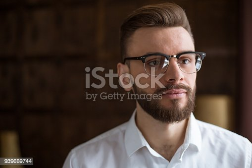 649754038 istock photo Young smiling handsome bearded businessman in a white shirt and glasses stands at the center of the office and looks at the camera. 939669744