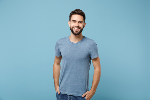 Young smiling handsome man in casual clothes posing isolated on blue wall background, studio portrait. People sincere emotions lifestyle concept. Mock up copy space. Holding hands in pockets