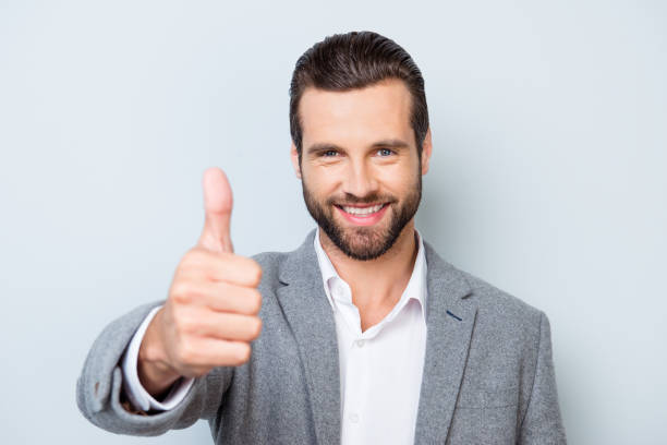 Young smiling handsome worker in formal clothing demonstrating thumb up against gray background stock photo