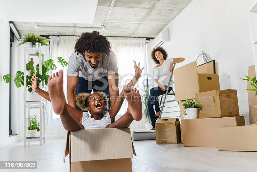 istock Young Smiling Happy African-american Family Unpacking During Move. New Home. 1167907809