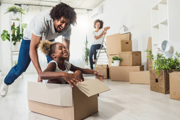 Junge lächelnd glückliche afroamerikanische Familie Auspacken während des Umzugs. Neues Zuhause. – Foto