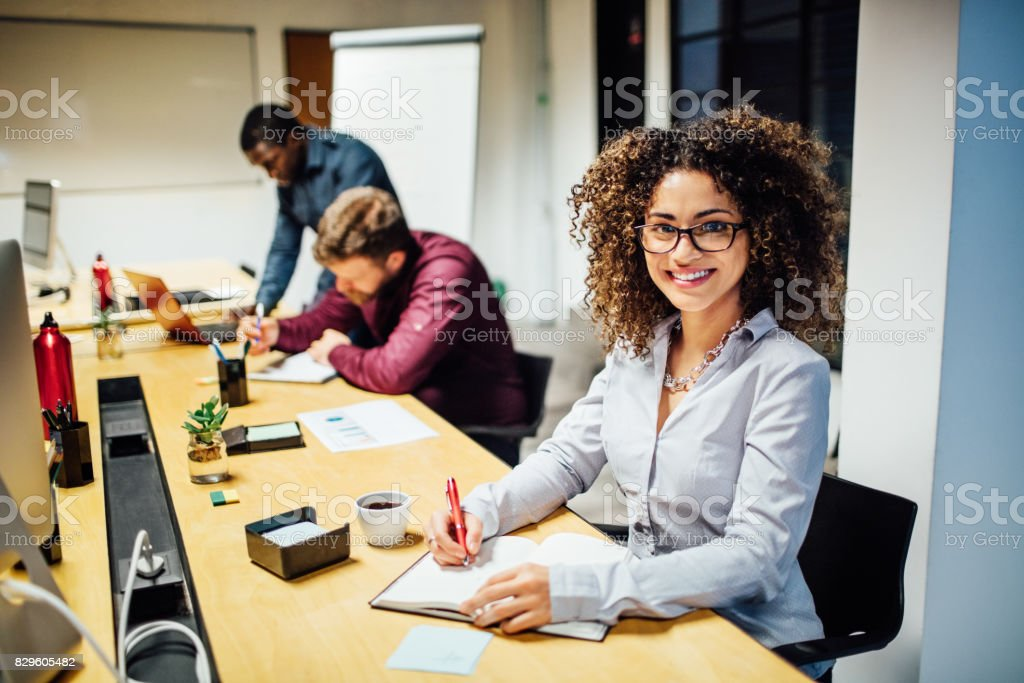 Young smiling hispanic woman working at startup stock photo