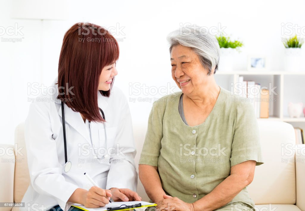 young smiling home caregiver  with senior woman stock photo