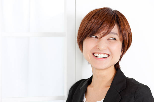 Young smiling Japanese woman looks away stock photo