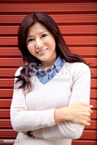 istock Young smiling Japanese woman on red background. 185306152