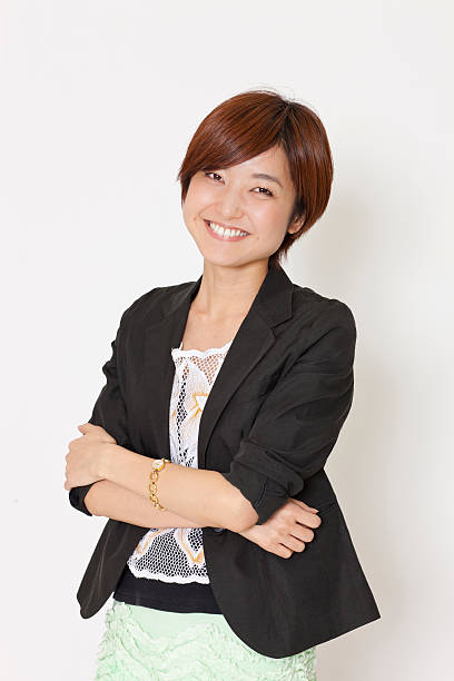 Young smiling Japanese woman with folded arms stock photo
