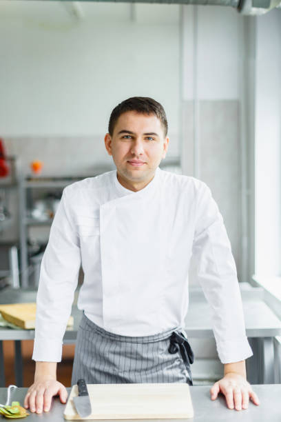 Young smiling male chef posing stock photo
