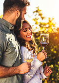 Young smiling couple tasting wine at winery vineyard - Friendship and love concept with young people enjoying harvest time