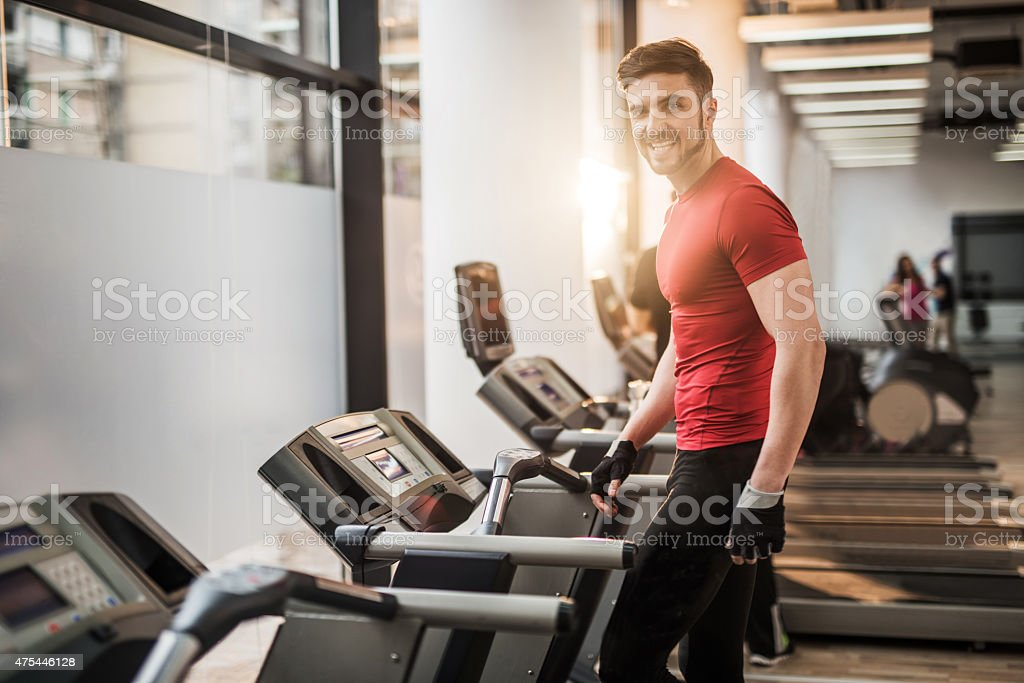 Young happy athlete walking on a treadmill in a gym and looking at...
