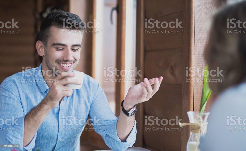 Young smiling man having a conversation on a coffee break stock photo
