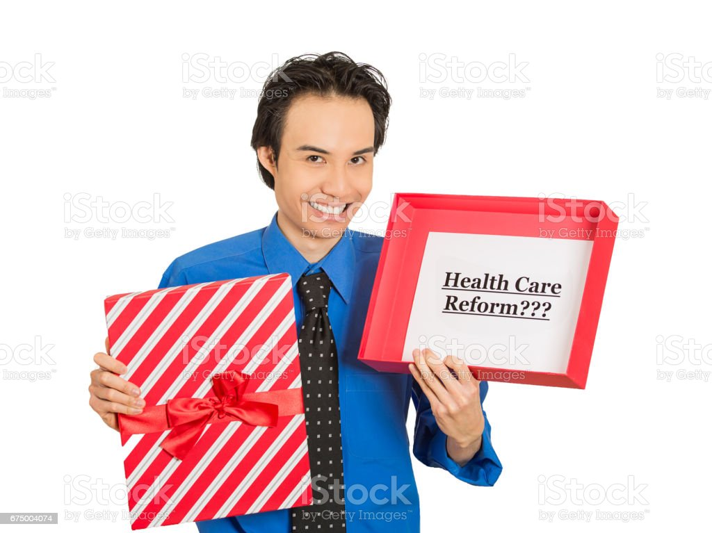 young smiling man holding sign health care reform in gift box, uncertain of universal insurance coverage plan stock photo