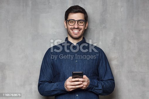 825083556istockphoto Young smiling man in denim shirt and trendy eyeglasses standing against gray textured wall, holding his phone with both hands 1165763875