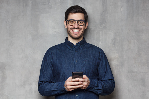 825083556 istock photo Young smiling man in denim shirt and trendy eyeglasses standing against gray textured wall, holding his phone with both hands 1165763875