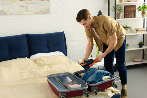 young smiling man packing clothes into travel bag stock photo