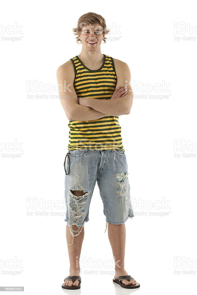 Young smiling man standing with arms crossed stock photo