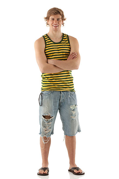 Young smiling man standing with arms crossed Young smiling man standing with arms crossedhttp://www.twodozendesign.info/i/1.png shorts stock pictures, royalty-free photos & images