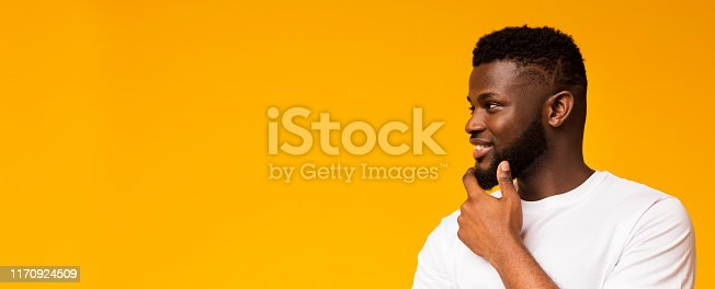 istock Young smiling man thinking and looking away on free space 1170924509