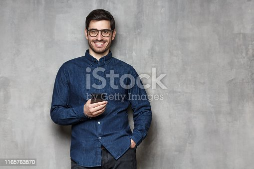 825083556istockphoto Young smiling man wearing denim shirt and trendy glasses standing against gray wall with mobile phone in one hand. Copy space on the right side 1165763870