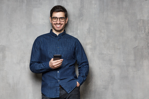 825083556 istock photo Young smiling man wearing denim shirt and trendy glasses standing against gray wall with mobile phone in one hand. Copy space on the right side 1165763870