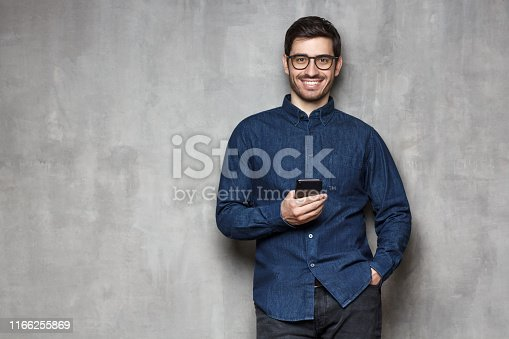 825083556istockphoto Young smiling man wearing denim shirt and trendy glasses standing against gray wall with cellphone in one hand. Copy space on the left side 1166255869