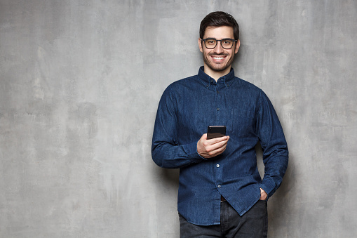 825083556 istock photo Young smiling man wearing denim shirt and trendy glasses standing against gray wall with cellphone in one hand. Copy space on the left side 1166255869