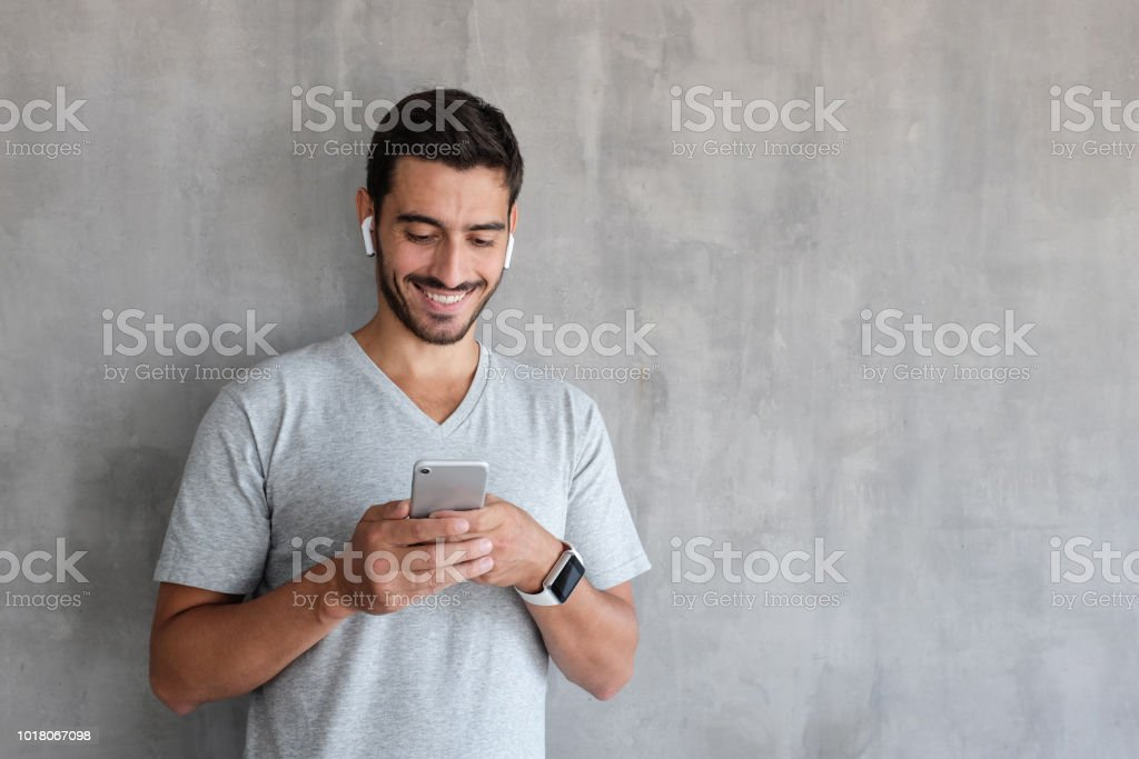 Young smiling man wearing wireless earphones and smart watches, standing against gray textured wall with copy space, looking at screen of smartphone stock photo
