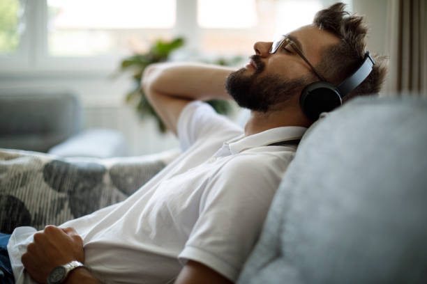 Young smiling man with bluetooth headphones relaxing on sofa stock photo