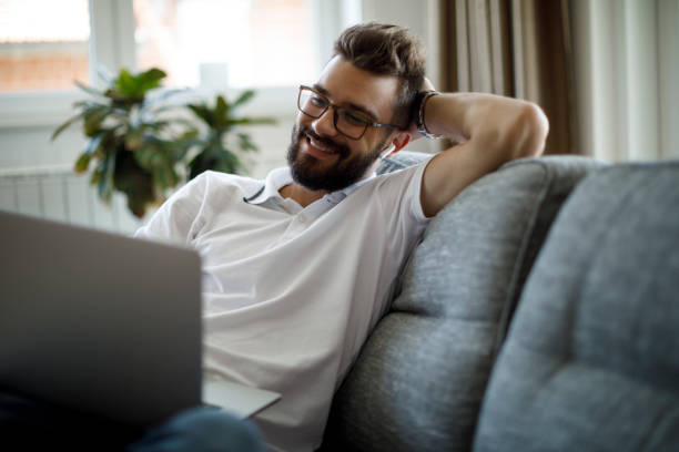 Young smiling man with bluetooth headphones using laptop at home stock photo
