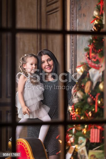 1061876006 istock photo Young smiling mother with cute little girl near a Christmas tree. Amazing family holiday concept. 938417692