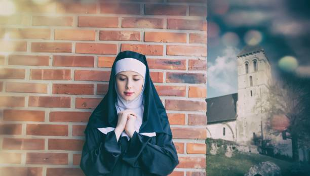 Young smiling nun standing near brick wall stock photo