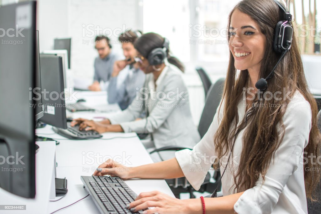 Young smiling operator woman agent with headsets working in a call centre. stock photo