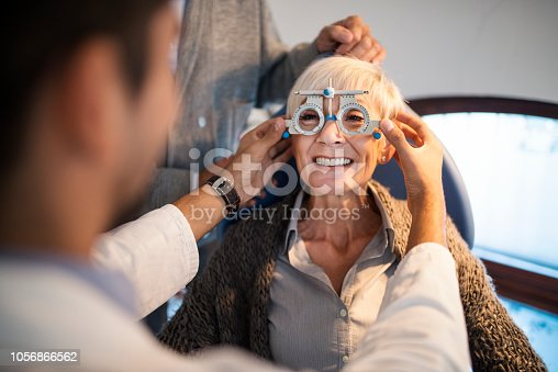 Senior woman having her eyesight checked by young optician at ophthalmologist's office.