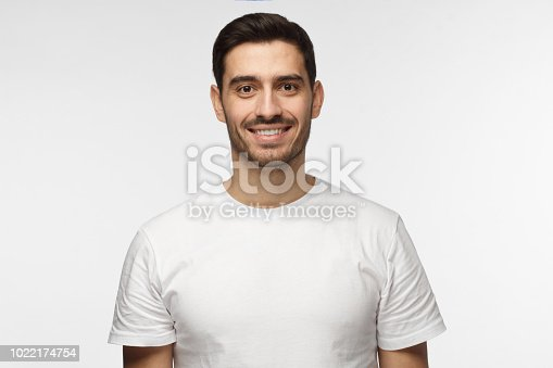 istock Young smiling optimistic man in blank white t-shirt standing isolated on light gray background 1022174754