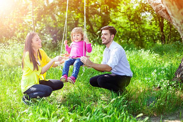 young smiling parents swinging their daughter in the park - mãe criança brincar relva efeito de refração de luz imagens e fotografias de stock