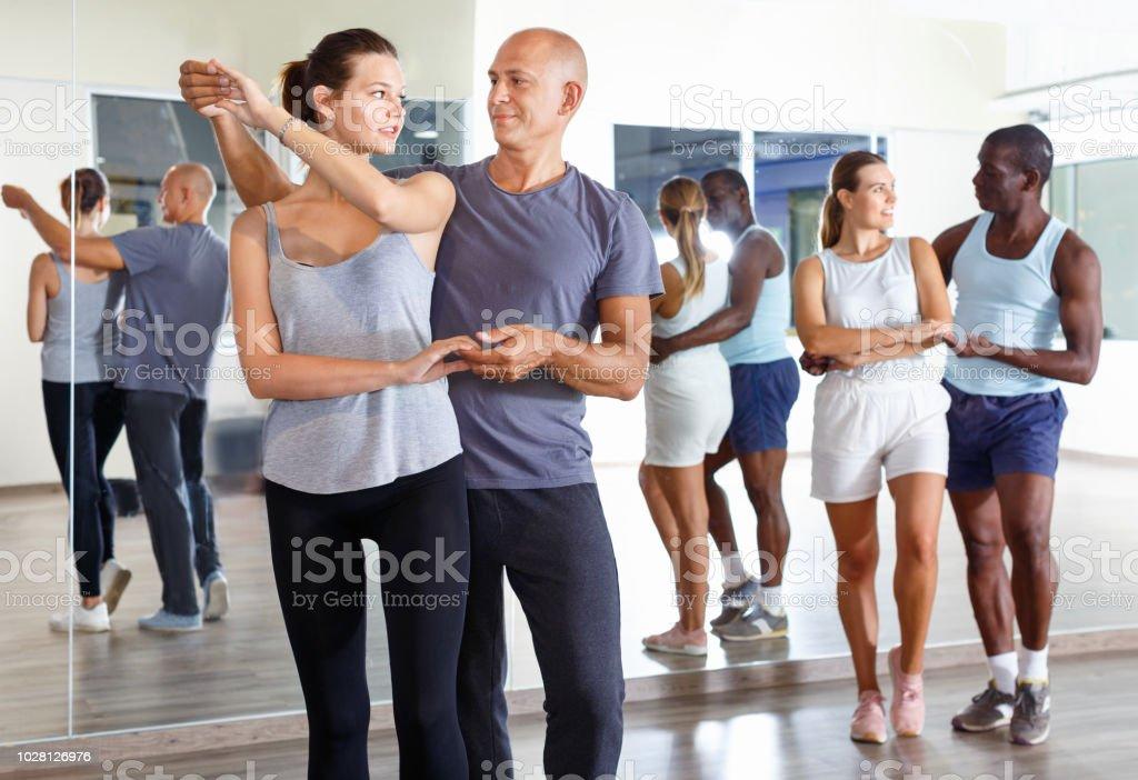 Jeunes souriant pratiquant samba passionnée dans les cours de danse - Photo