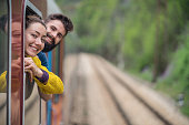 Excited young couple travelling by train in the country and standing out of the window