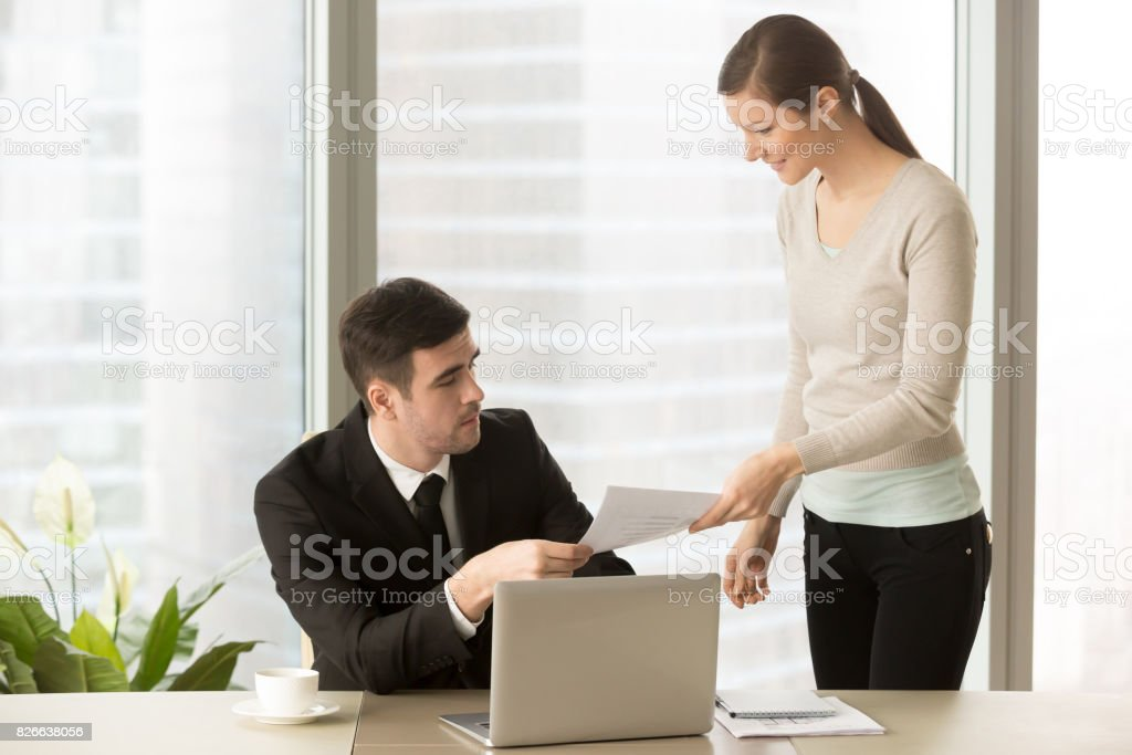 Young smiling personal assistant giving document to boss, paperwork reporting stock photo