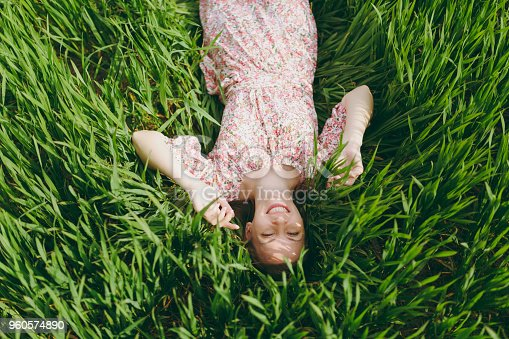 istock Young smiling pretty woman in light patterned dress lying on grass spreading hands looking up resting in sunny weather in field on bright green background. Spring nature. Lifestyle, leisure concept. 960574890