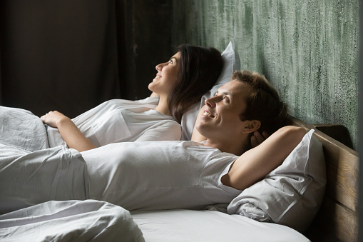 973962076 istock photo Young smiling satisfied couple in love lying in bed 1059754920