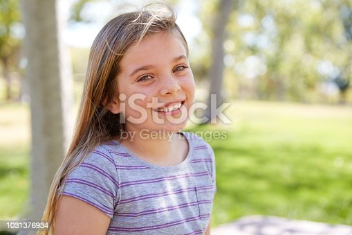 Young smiling schoolgirl looking to camera, close up portrait