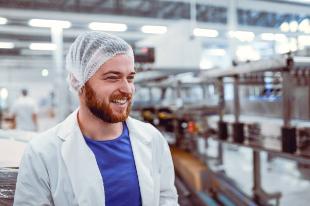 Young Smiling Scientist Posing in Modern Factory Young Smiling Scientist Posing in Modern Factory hair net stock pictures, royalty-free photos & images