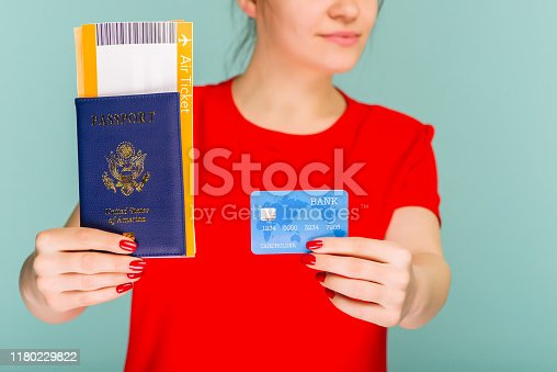Young smiling excited woman student holding passport boarding pass ticket and credit card isolated on blue background. Air travel flight - Image